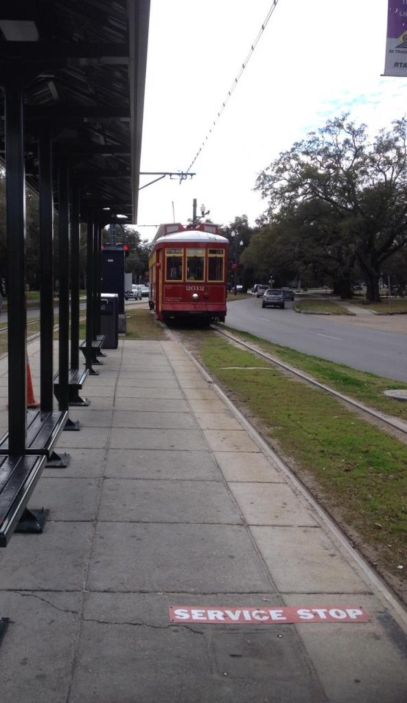 Red streetcar on Canal Street line approaching a stop