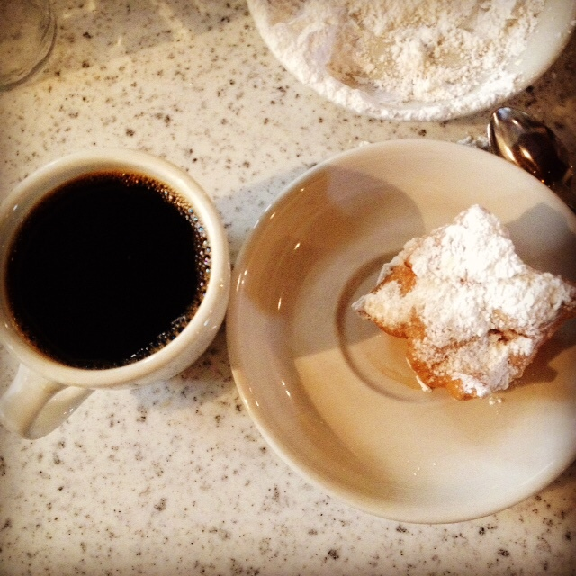 Black coffee and beignet covered in powdered sugar at Cafe Du Monde