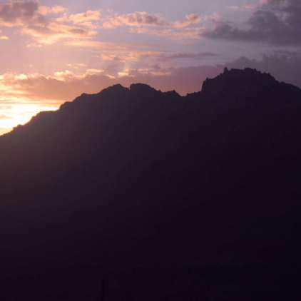 Purple and pink sunrise over rocky hill in Marble Canyon, Arizona