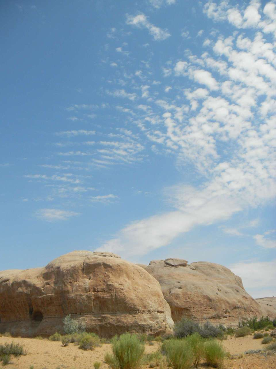 Rock formations, dry arid land, wispy clouds