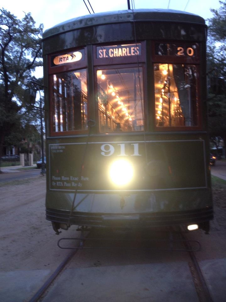 Dark green St. Charles streetcar with bright headlight shining