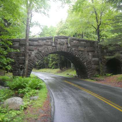 Stone bridge, over wet paved road, in Acadia National Park